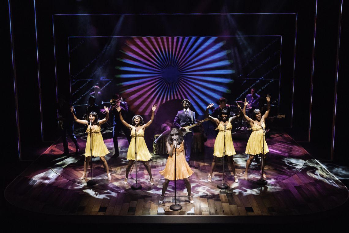 Tina singt auf Bühne mit Background Sängerinnen im Musical mit gelben Kleid